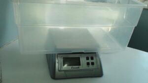 FIGURE 2. Simple plastic container placed on a digital scale to weigh small exotic pets.